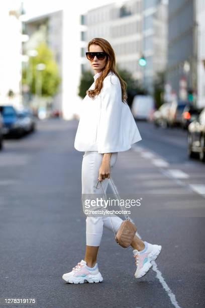 Actress and model Rebecca Kunikowski wearing a light pink top by Zara, a white blazer with slits by Zara, white pants by Zara, a beige bag by Weat,...