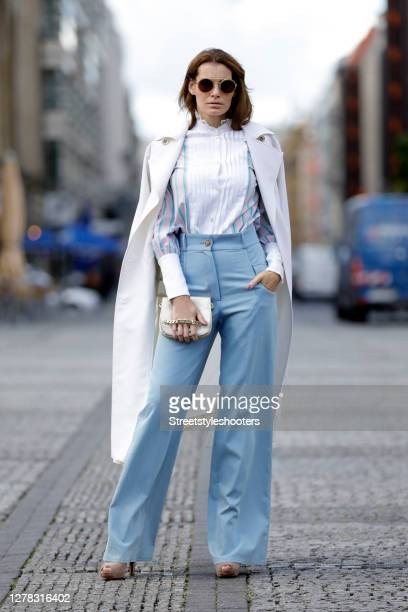 Actress and model Rebecca Kunikowski wearing sunglasses by Thomas Sabo, a long white coat by Marcel Ostertag, light blue high waisted pants Marcel...