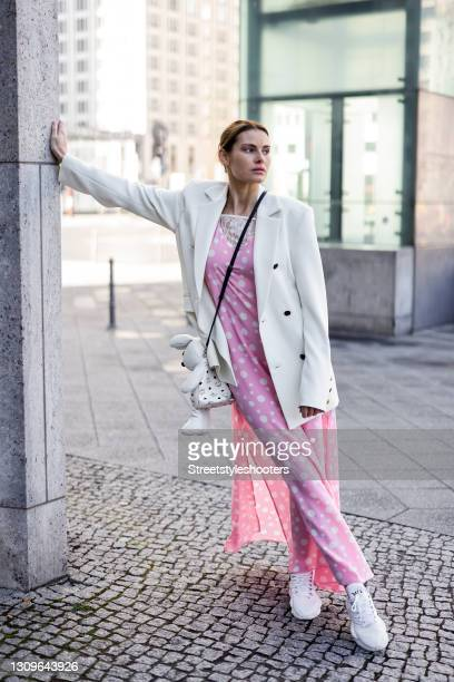 Actress and model Rebecca Kunikowski wearing white sneaker by Y-3, a pastel pink maxi dress with white polka dots and lace detail by Marcel Ostertag,...