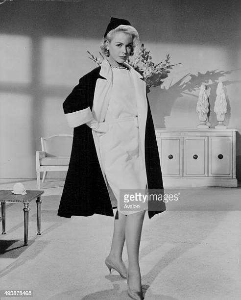 Actress and model Sandra Dee, modeling a full length black linen coat with white lining, and a white dress, 1963.