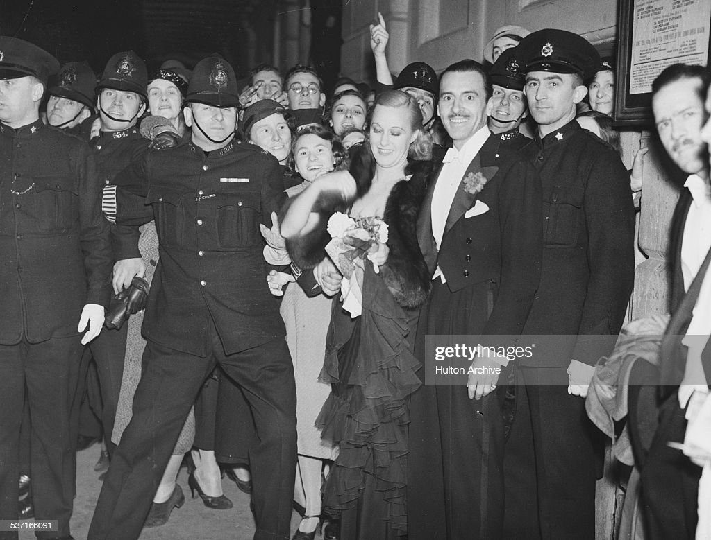 Actress and operatic soprano singer Grace Moore and her husband Valentin Parera, being protected from a crowd of fans by police officers as they leave a theatre, circa 1940.