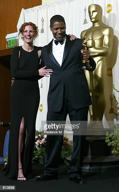 Actress and presenter Julia Roberts and actor Denzel Washington pose with his Best Actor in a Leading Role Award for 'Training Day' backstage during...