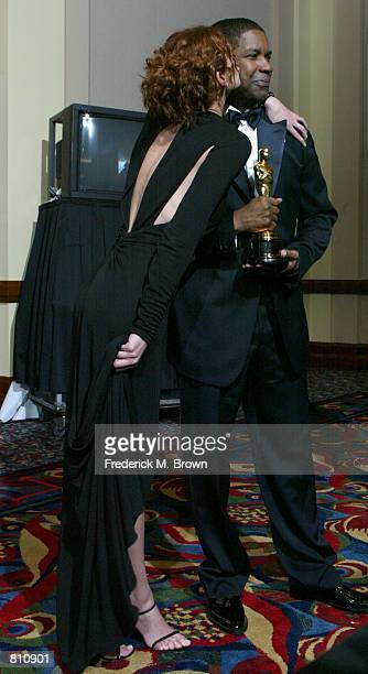 Actress and presenter Julia Roberts kisses Best Actor in a Leading Role winner Denzel Washington for 'Training Day' backstage during the 74th Annual...