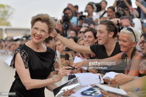 US actress and president of the jury Annette Bening signs autographs as she arrives for the opening ceremony of the 74th Venice Film Festival and the...