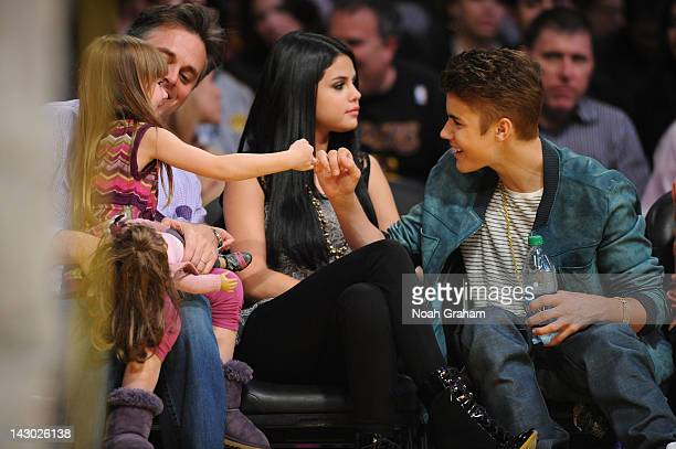 Actress and recording artist Selena Gomez and boyfriend Justin Bieber interact with fans during a game between the San Antonio Spurs and the Los...