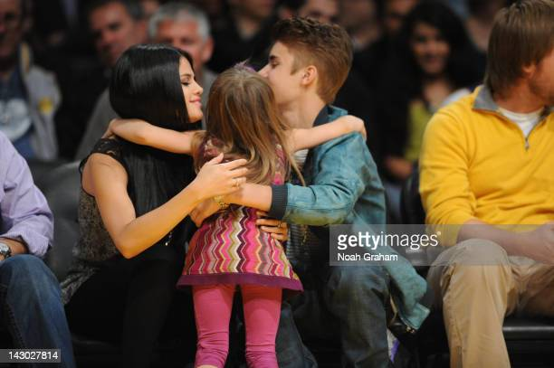 Actress and recording artist Selena Gomez and boyfriend Justin Bieber get a hug from a young fan during a game between the San Antonio Spurs and the...