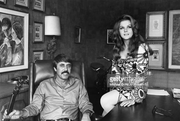 Actress and singer AnnMargret and singer songwriter and producer Lee Hazlewood pose for a portrait in his office in 1969 in Los Angeles California