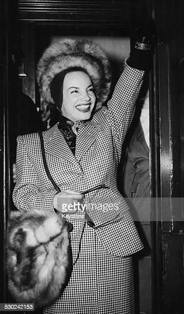 Actress and singer Carmen Miranda waving as she arrives at Waterloo Station London April 21st 1948