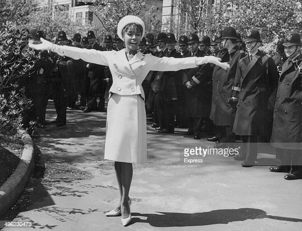 Actress and singer Diahann Carroll posing for photographers flanked by policemen at the May Day Parade in Embankment Gardens London circa 19601970