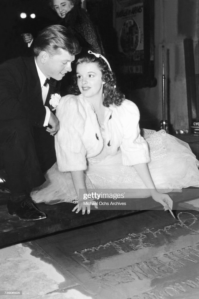 Actress and singer Judy Garland with actor Mickey Rooney leaves her hand and footprints in cement outside Grauman's Chinese Theatre on October 10, 1939 in Los Angeles, California.