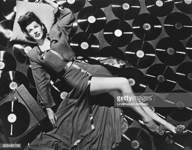 Actress and singer Marie 'The Body' McDonald lies seductively on the floor surrounded by record albums of 'Liebestraum' by composer Franz Liszt...