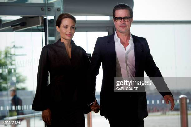 US actress and special UN envoy Angelina Jolie and her husband US actor Brad Pitt pose for pictures upon arrival on the fourth day of the Global...