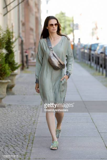 Actress and TV host Katrin Wrobel wearing a green dress and a platin colored beltbag by Lendsdorf, green sandals by Mime et moi x Anna van den Hoevel...