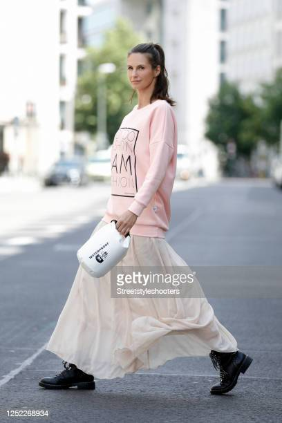 Actress and TV host Katrin Wrobel wearing a pasel pink pullover with black front print by Ohnegleichen a beige long maxi skirt black boots by Bruno...