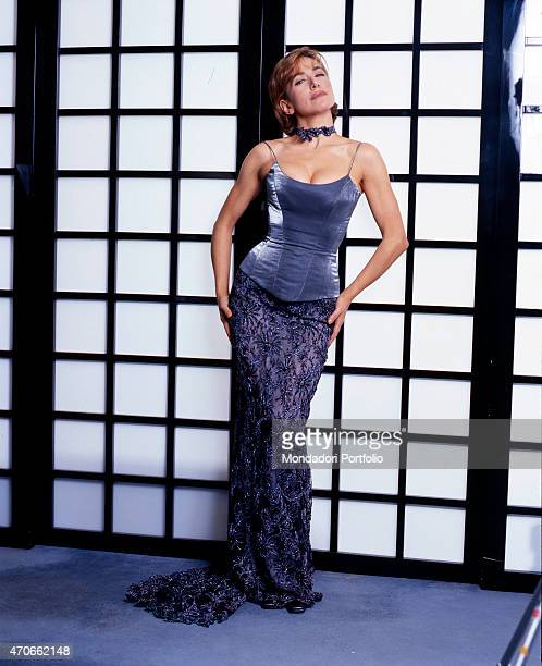 Actress and TV hostess Barbara d'Urso wears an elegant dress in indigo colored silk in a sexy pose before a curtain wall many are her professional...