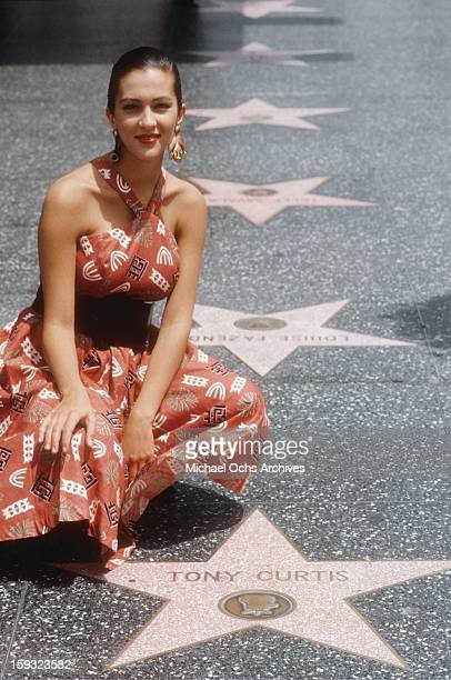 Actress and TV personality Allegra Curtis poses for a portrait next to her father's star on Hollywood Boulevard in 1988 in Los Angeles California