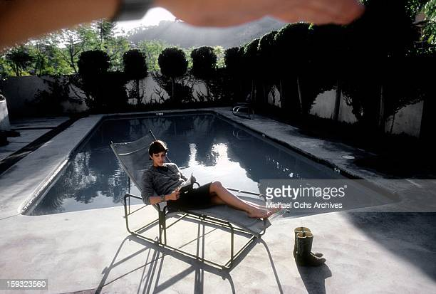 Actress and TV personality Allegra Curtis reads by the pool at home in January 1982 in Los Angeles California