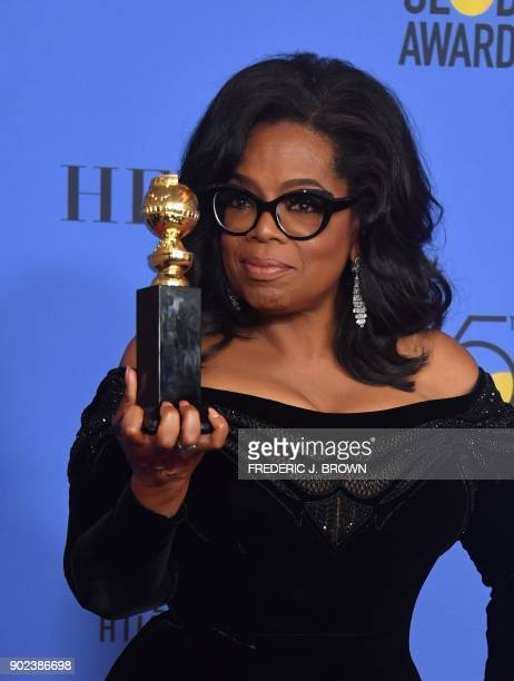 TOPSHOT Actress and TV talk show host Oprah Winfrey poses with the Cecil B DeMille Award during the 75th Golden Globe Awards on January 7 in Beverly...