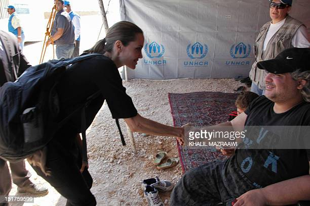 Actress and UNHCR special envoy Angelina Jolie shakes hands with a Syrian refugee during her visit to the Zaatari refugee camp near the Jordanian...