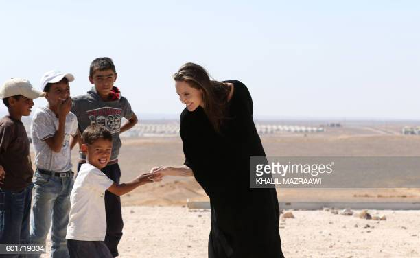 Actress and UNHCR special envoy Angelina Jolie talks to children during a visit to a Syrian refugee camp in Azraq in northern Jordan, on September 9,...