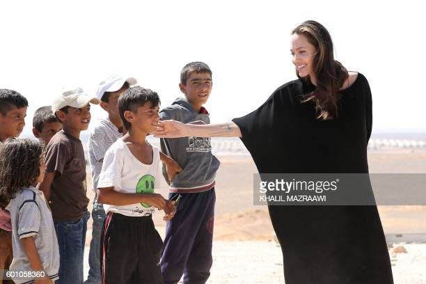 Actress and UNHCR special envoy Angelina Jolie talks to children as she arrives at a Syrian refugee camp in Azraq in northern Jordan, on September 9,...