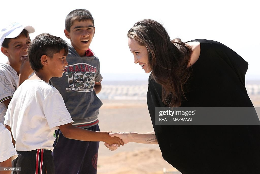 US actress and UNHCR special envoy Angelina Jolie talks to children as she arrives at a Syrian refugee camp in Azraq in northern Jordan, on September 9, 2016. / AFP / Khalil MAZRAAWI