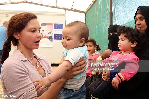 US actress and United Nations Population Fund's Goodwill Ambassador Ashley Judd carries a Syrian child during a visit at the Zaatari refugee camp...