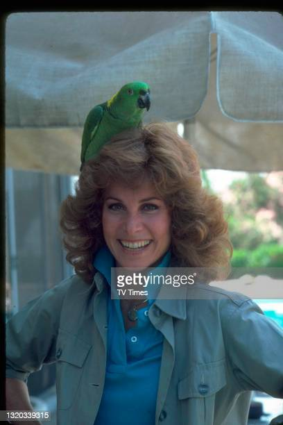 Actress and wildlife conservationist Stefanie Powers photographed with a yellow-naped amazon parrot on her head, circa 1982.