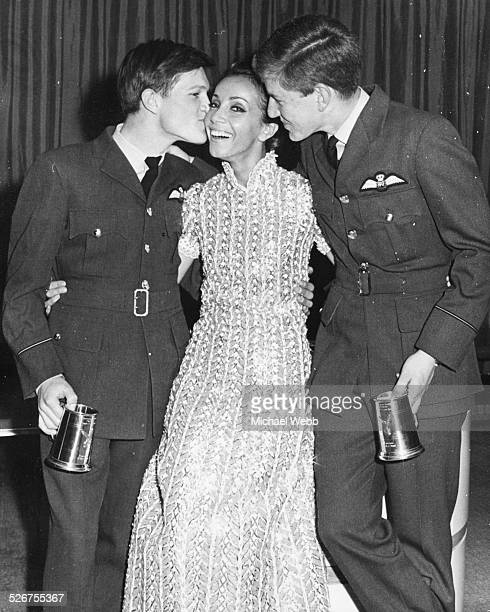 Actress Andrea Parisy being kissed on the cheek by Pilot-Officer Jeremy Dent and Pilot-Officer Ron Dowler at the premiere of the film 'Don't Look...