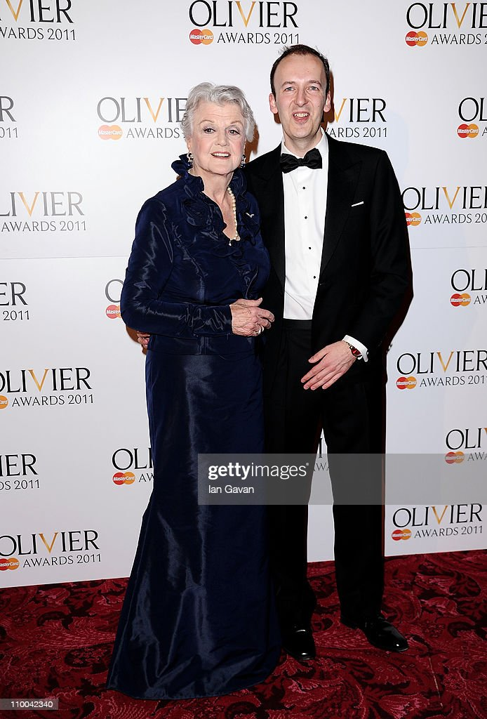 Actress Angela Lansbury and Julian Bird pose in the press room during The Olivier Awards 2011 at Theatre Royal on March 13, 2011 in London, England.