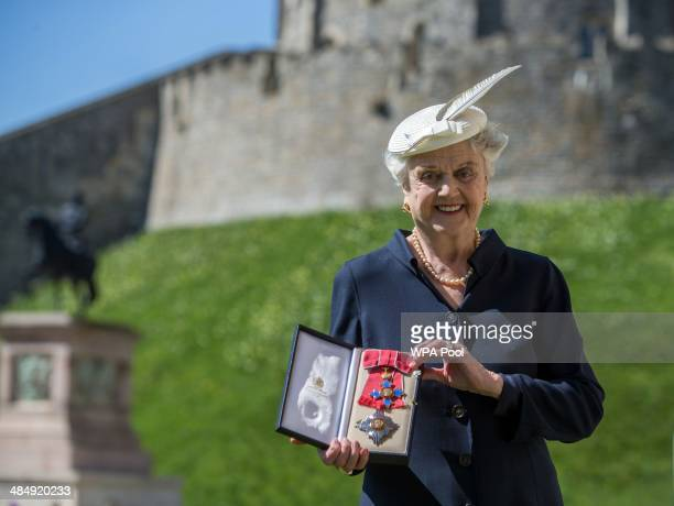 Actress Angela Lansbury poses with her Dame Commander medal given to her by Queen Elizabeth II at an Investiture ceremony at Windsor Castle on April...