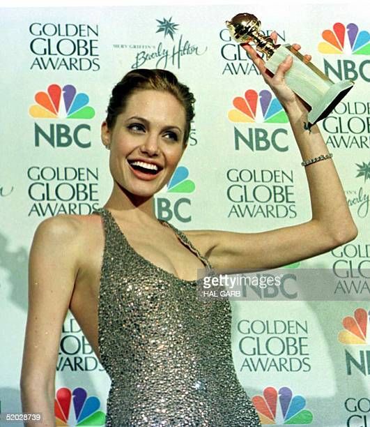 Actress Angelina Jolie holds her Golden Globe award for Best Actress in a TV Movie for her role in 'Gia' at the 56th Annual Golden Globe Awards in...