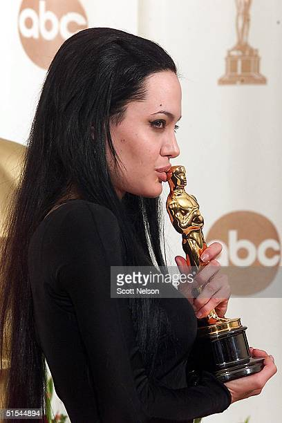 Actress Angelina Jolie kisses her Oscar at the Academy Awards in Los Angeles 26 March 2000 Jolie won for Best Supporting Actress for her role in...