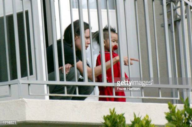 Actress Angelina Jolie plays with her son Maddox on the balcony of a hotel on December 30 2002 in Beverly Hills California