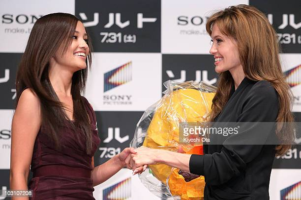 Actress Angelina Jolie shakes hands with actress Meisa Kuroki as she receives a bouquet of flowers during the 'Salt' press conference at Grand Hyatt...