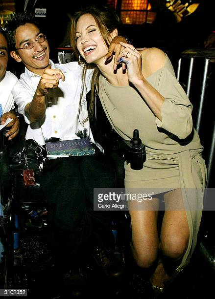 Actress Angelina Jolie signs autographs for a man in a wheelchair as she arrives for the world premiere of her film 'Taking Lives' March 16 2004 in...