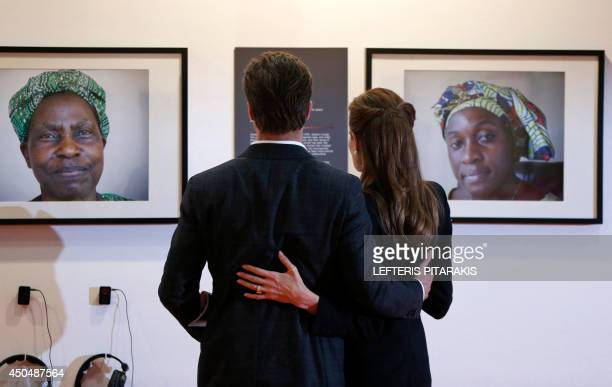 US actress Angelina Jolie Special Envoy for the United Nations High Commissioner for Refugees and her partner US actor Brad Pitt look at displayed...
