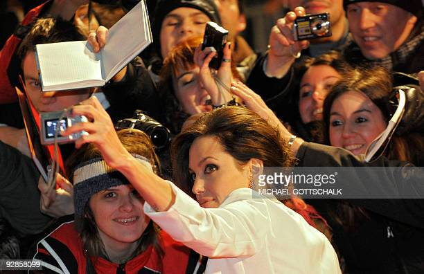 US actress Angelina Jolie takes a picture of her with fan on the red carpet for the German premiere of the film �The Curious Case of Benjamin Button�...
