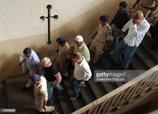 US actress Angelina Jolie's bodyguards Michael John Brett Robert Patrick Dunn and Tomas McAdanc walk at the Azad Maidan Police Station soon after...