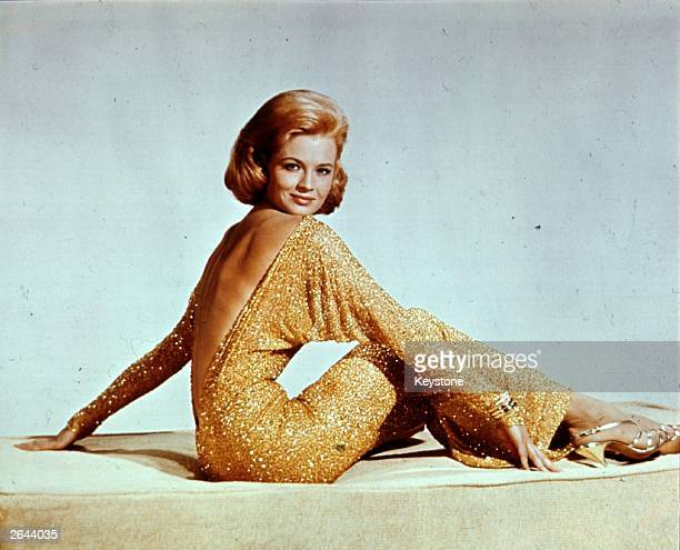 US actress Angie Dickinson wearing a backless gold lame evening dress with batwing sleeves