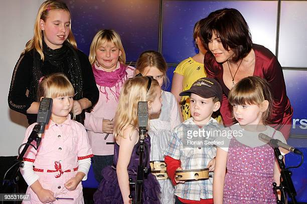 Actress Anja Kruse and children pose on stage at the launch of the BMW art advent calendar 2009 at a BMW branch on December 1, 2009 in Berlin,...