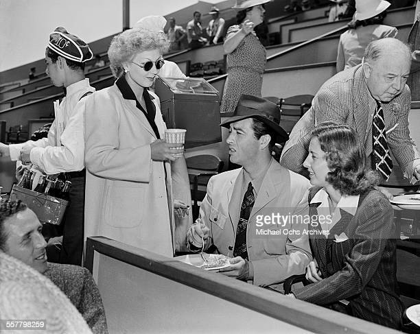 Actress Ann Sothern talks with actor Robert Taylor and actress Barbara Stanwyck during a tennis match in Los Angeles California