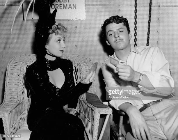 Actress Ann Sothern tries out a card trick on costar John Carroll on the set of the MGM film 'Congo Maisie' 1939