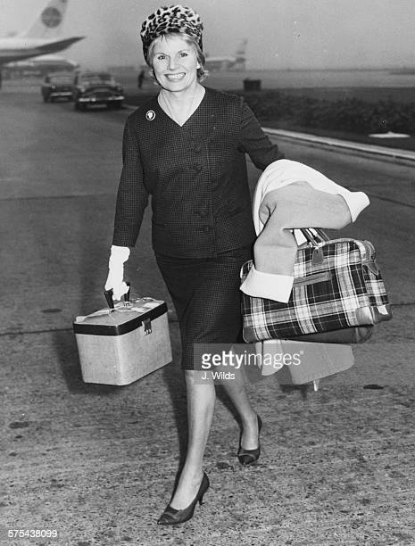 Actress Ann Todd smiling as she carries her luggage from the plane at London Airport October 13th 1961