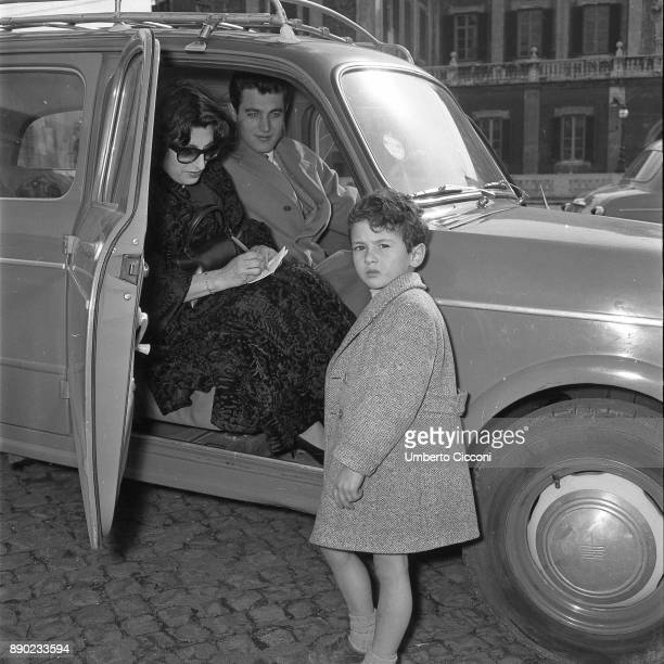 Actress Anna Magnani makes an autograph while she is is with actor Gabriele Tinti and a child in front of the Quirinal Palace Rome 1957