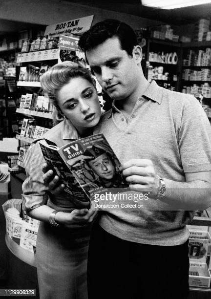 Actress Anna Maria Alberghetti and Buddy Bregman look at a TV Guide during portrait session at home in 1958