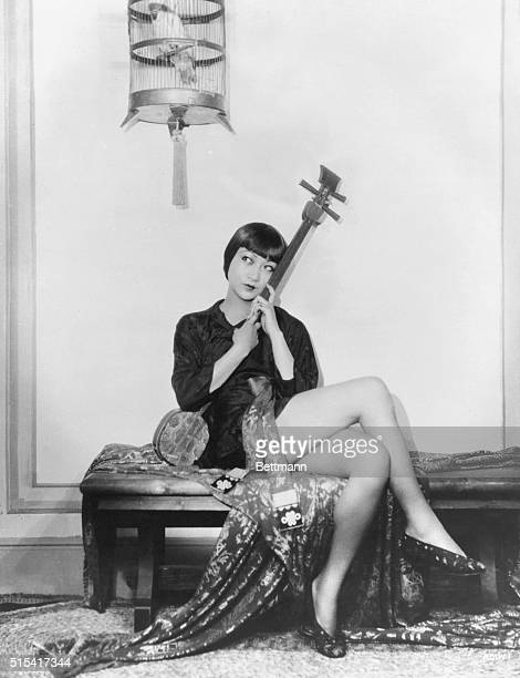 Actress Anna May Wong holding a Japanese shamisen and sitting underneath a caged bird