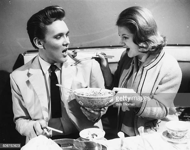 Actress Anna Palk feeding Chinese food to singer Billy Fury during a break in filming 'Play it Cool' at Pinewood Studios London February 13th 1962