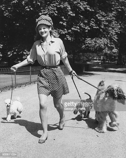 Actress Anna Palk smiling as she walks her three pet dogs in Hyde Park London July 20th 1967