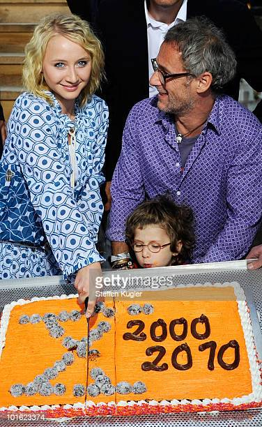 Actress AnnaMaria Muehe and Dani Levy with his son Joshi cut the birthday cake at the 10 Years XVerleih reception on June 4 2010 in Berlin Germany